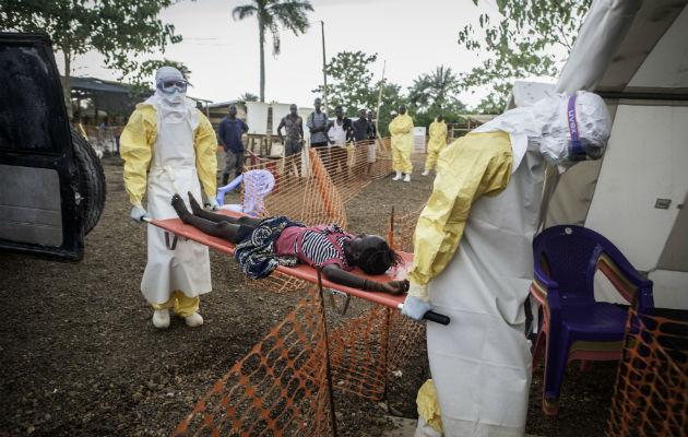 Pigen på båren er blevet syg, og siden hun har været i kontakt med ebola-smittede, bliver hun bragt til vores ebola-center i Kailahun i Sierra Leone. (arkivfoto 9.juli 2014) © Sylvain Cherkaoui/Cosmos.